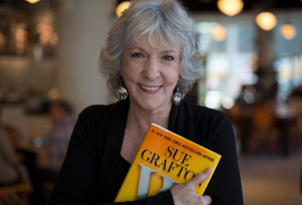 """TORONTO, ON - OCTOBER 3: Detective novelist Sue Grafton poses with her 23rd book """"W"""" at a coffee shop in the Toronto Reference Library, October 3, 2013. (Chris So/Toronto Star via Getty Images)"""